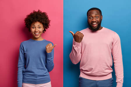 Photo of happy black woman and man spouse point thumbs at each other, have good mood, suggests to choose one of them, smile happily, isolated over blue and pink background, say its your affair Stock fotó