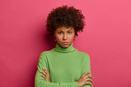 Serious looking offended woman looks angrily at camera, keeps arms folded, smirks face, doesnt trust person, dressed casually, isolated on pink wall, dislikes suspicious idea, disagrees with someone