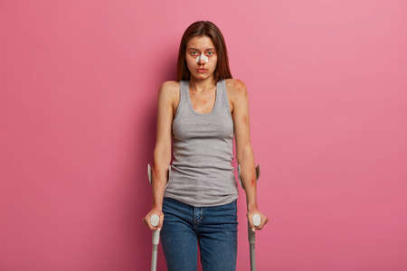 Bruised unhappy woman got into serious road traffic accident, has various injuries on body, broken nose, walks with crutches for mobility assistance, has recovery period, prepares for surgery.