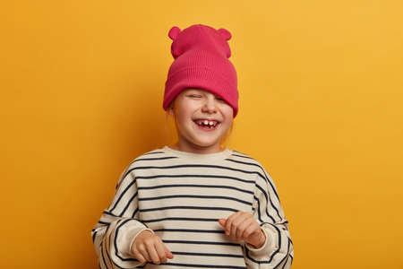 Sincere emotional child plays with new hat, dressed in striped jumper, laughs and cheers something, has funny joyful expression, playful mood, going crazy, isolated on vibrant yellow background