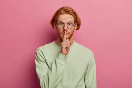 Shush, be silent. Bearded ginger man makes hush hand sign, keeps index finger to lips, tells secret information, gossips about something, wears optical glasses and jumper, looks mysteriously