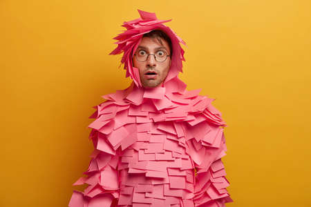 Indoor shot of shocked young Caucasian man stares with bugged eyes, wears transparent glasses, has creative costume made of sticky notes, stares startled and impressed, isolated over yellow wall