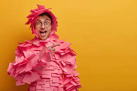 Positive funny man indicates on blank space at upper right corner, advertises some product, wears outfit made of adhesive notes, round spectacles, isolated over yellow background. Look at this
