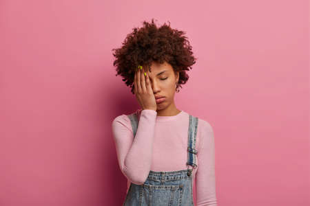 Fatigue curly haired woman feels bored and distressed, wants to sleep, covers half of face with palm, keeps eyes shut, wears fashionable clothes, poses against pink background. Tiredness concept