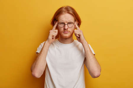 Distressed redhead man presses fingers to temples, has helpless face expression, suffers from severe headache, tries to remember important information, sees no way out, grimaces because of bad mistake