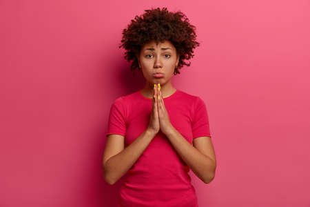 Frustrated unhappy curly haired woman begs for permission, keeps palms pressed together, purses lower lip, asks for pray and apology, says I am very sorry and forgive me, wears bright pink t shirt