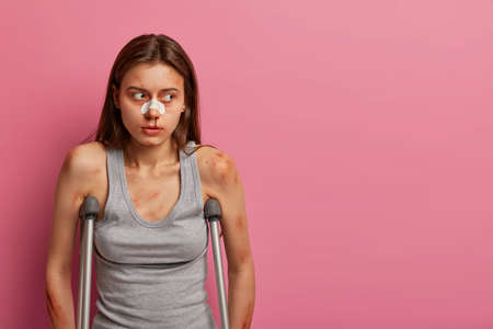 Consequences of dangerous accident. Displeased unhappy woman fell off ladder, has bandage on nose, stands on crutches, being on sick leave, claims about painful feelings. Crashing during driving