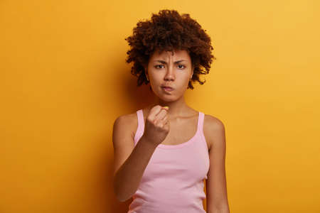 Indoor shot of displeased dark skinned woman has serious look, shows clenched fist at camera, threatens someone, expresses aggression with body language, wears casual tank top, isolated on yellow wall Banque d'images