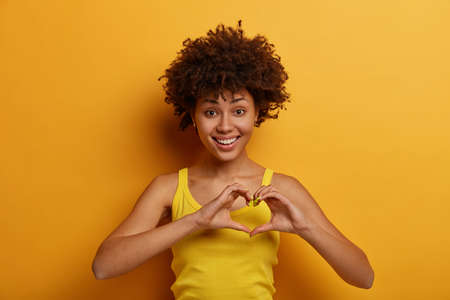 Isolated shot of pleasant looking woman makes heart gesture, says be my valentine, smiles positively, expresses love and care, fell in love with someone, wears yellow shirt, stands indoor alone.
