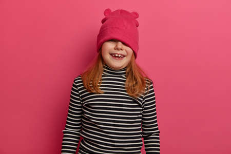 Waist up shot of adorable girl has playful mood, looks from above hat, foolishes around, wears striped poloneck, has broad smille, poses against rosy background, being disobedient or naughty