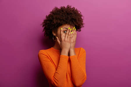 Young ethnic woman peeks through fingers, hides face with palms, has bright manicure, afraids of seeing something, wears casual orange sweater, stands against purple wall eager to see prepared present Stock Photo