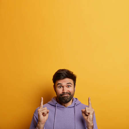 Puzzled hesitant man with beard, presses lips, wears violet hoodie, points index fingers above, hesitates what to buy, has clueless expression, isolated on yellow background, blank space upwards