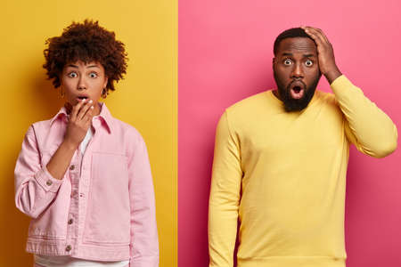 Shocked black female and male stare at camera, expresses great surprisement, open mouthes, hear unbelievable news, wear pastel pink and yellow clothes, stand together in studio. Oh no, how scary.