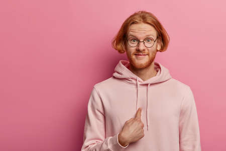 Optimistic red haired man with beard, tells he is perfect candidate, volunteers and wills to participate, looks with joyful expression, wears sweatshirt, isolated over pink wall, copy space. Stock fotó