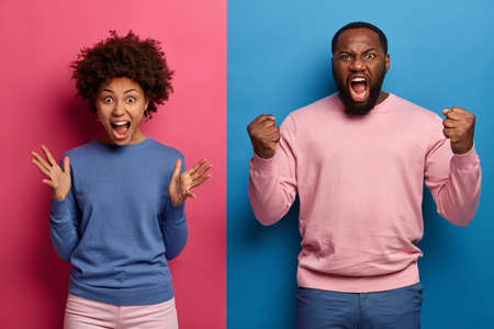 Photo of annoyed rude woman and man scream with agression, grimace and gesture angrily, dont agree with not fair situation, roar loudly I will kiss you, stand against two color studio background