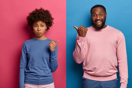 Sad ethnic woman and happy man point thumbs at each other, have quarrel or argument, blame and sort out relationship, stand closely against pink and blue studio wall. Human emotions concept. Stock Photo