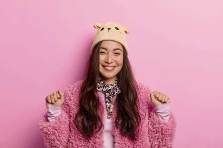 Magnificent lovely girl keeps hands clenched in fists, shows luck gesture, smiles happily as hears good news, gets nice suggestion to spend free time, dressed in coat and headgear, poses indoor
