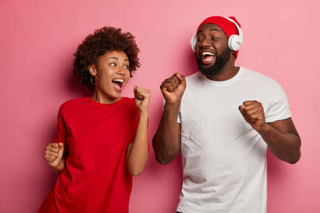 Half length shot of overjoyed ethnic curly woman and man raises clenched fists, have fun together, look happily at each other, feel rhythm of music, pose over pink background, move in studio Stock Photo