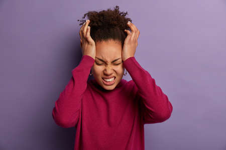 Photo of dissatisfied woman keeps hands on temple, suffers from unbearable headache, clenches teeth with pain, being exhausted after work, wears burgundy turtleneck, isolated on purple wall.
