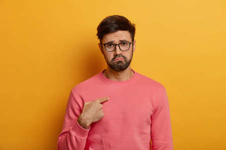 Disappointed upset adult man points at himself, displeased being chosen to punish, has gloomy expression, says you talking to me, wears pink sweater, eyewear. Negative face expressions concept