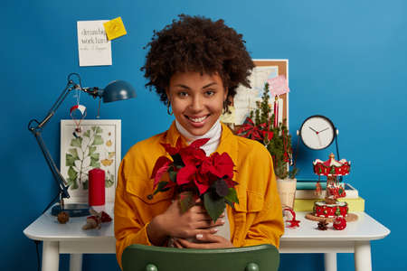 Happy Afro American woman sits at comfortable chair in coworking space, embraces pot with plant, smiles positively, finishes work in time, wears yellow jacket, blue walls with sticky informative notes