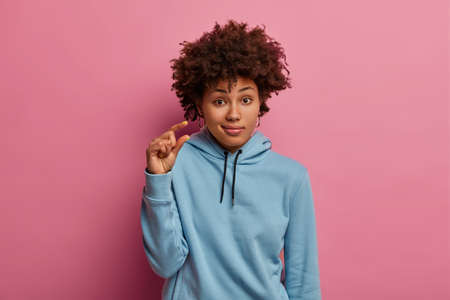 Puzzled dark skinned woman shapes item with small size, shows tiny sign, wears blue hoodie, looks unimpressed, isolated over pink pastel background, says so little. People and body language concept