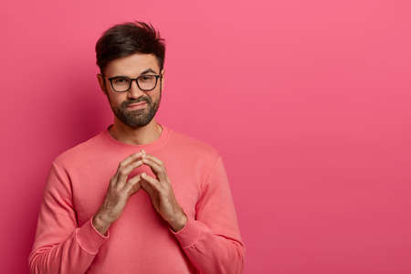 Handsome unshaven man has tricky evil plan, steepls fingers and looks mysteriously at camera, thinks over good idea, wears casual sweater and spectacles, poses over rosy background, copy space