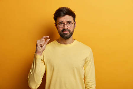 Disappointed adult man shows small size, measures something very tiny with fingers, shows insufficient length or thickness, discusses dicreased prices, dressed in casual clothes, poses indoor