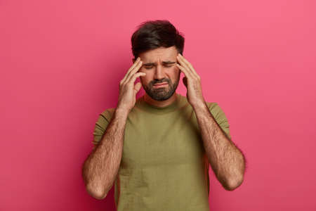Exhausted man touches temples with closed eyes, suffers from headache, waits someone bring painkillers, wears t shirt, has bad day, isolated over pink background, bothered with painful disease