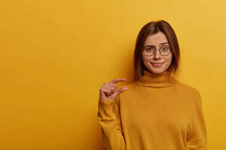 Indoor shot of displeased cute woman makes little size gesture, shapes something very small, wears round spectacles and yellow turtleneck, stands indoor over vivid wall. It costs me not much efforts