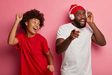 Good humored dark skinned couple fool around during photoshoot, dance at disco party with smiles, enjoy favourite music, relax with songs, guy wears headphones, points at you, isolated on pink wall Stock Photo