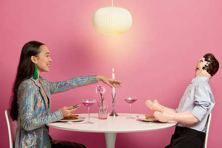 Unreal feelings and relations. Pleased woman finds lover via online matching application, holds mobile phone, stretches hand to imaginary boyfriend, imitates having date, pose at festive dinner table