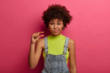 Displeased dark skinned woman has lack of time, shapes small or tiny object, wears casual clothes, explains how interested she was, has discontent expression, isolated over bright pink background