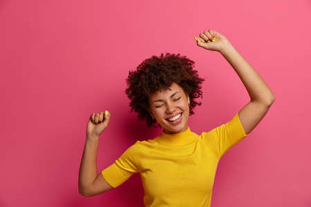 Beautiful dark skinned young woman feels relaxed and relieved, dances carefree, raises arms in air, smiles positively, dressed casually, poses against pink background. Happy lifestyle concept