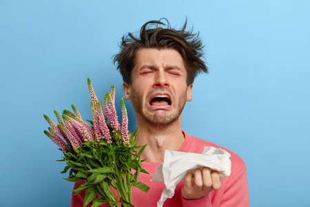 Miserable man in depression suffers from allergic malaise and rhinitis, seasonal disease, tired of sneezing, has red nose and eyes, allergy to flowering, holds handkerchief, feels irritation Stok Fotoğraf
