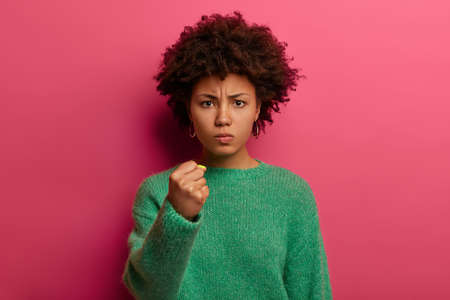 Portrait of short haired angry woman shows fist, has irritated expression, promises to revenge, wears green sweater, poses against pink background, domineers and threatens, being dissatisfied