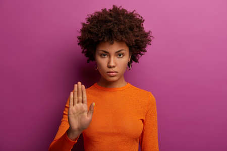 Enough please. Serious strict woman makes stop gesture, shows prohibition and asks hold on, rejects something, wears orange sweater, isolated on purple background. No means never, not into it