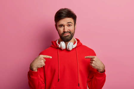 Unimpressed unshaven Caucasian guy points at himself, asks who me, has calm face expression, wears red sweatshirt, listens audio via headset, shows new bought outfit, poses over pink background Stock fotó