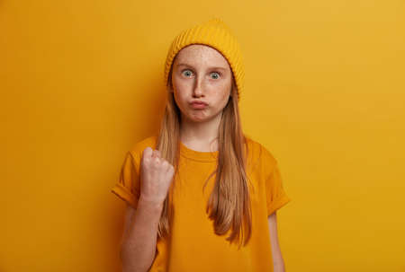 Portrait of emotional angry teenage girl shows fist, threatens you, pouts lips and has widely opened eyes, wears bright yellow clothes, poses indoor. Furious child gestures indoor. Childhood concept Banco de Imagens