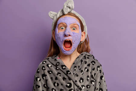 Emotive small ginger girl stares at camera with surprised expression, widely opened mouth, applies purple bubble mask, wears robe and headband, poses indoor, screams loudly, cares about beauty