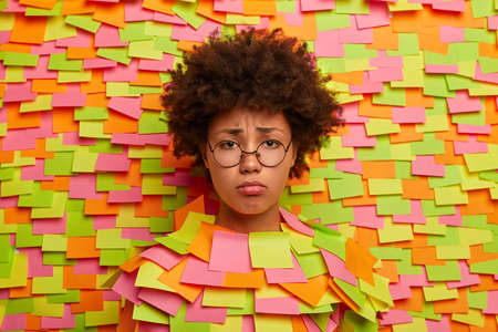 Unhappy distressed Afro American woman thinks about something troublesome, wants to cry, feels bad and offended, being insulted, wears round eyewear. Head through wall with colored stickers. 版權商用圖片