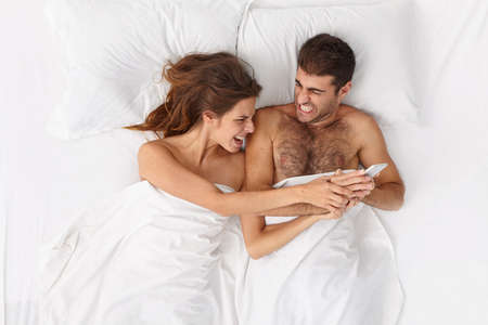 Depressed woman irritated with husband technology addiction, asks to give her smartphone, lie in bed, sort out relationship, clench teeth from annoyance, sleep under white blanket. Overhead shot.