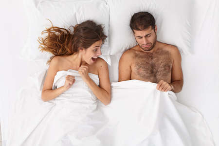 Curious excited woman looks at mans genital while lie in bed together. Displeased man looks under white blanket at penis, suffers from dysfunction. Sex problems, marriage, relationship concept