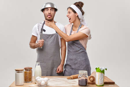 Angry woman keeps hands on husbands neck, irritated with inexperienced chef on kitchen, prepare something delicious together. Funny man with bowl on head and whisk in hand wears apron, learns to cook