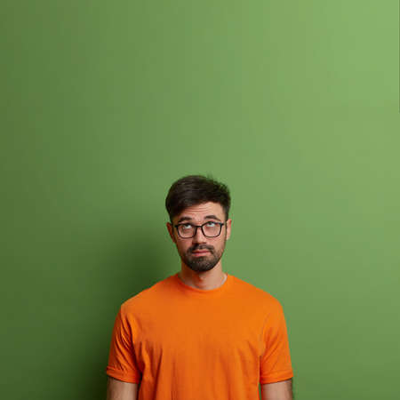 Serious bearded adult man concentrated above on blank copy space, wears eyewear and t shirt, thinks about buying something, isolated on green background. Vertical studio shot. Deep thoughts.