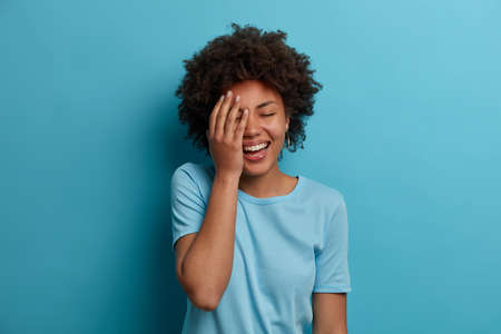 Horizontal shot of happy dark skinned woman makes face palm, giggles positively, keeps eyes closed, has good mood, wears blue t shirt, poses indoor, hears amazing info, reacts to lucky fine situation Stock fotó
