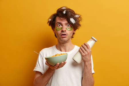 Photo of young man eats cornflakes with milk for breakfast, stares with bugged eyes as hears shocking news in morning, has healthy nutrition, cares about eye skin, wears patches for reducing wrinkles