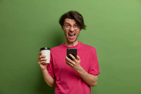Crazy man shouts loudly, holds coffee in paper cup, uses modern smartphone, surfs web, annoyed to get bad message, dressed in pink t shirt, dissatisfied after talking with boring interloctor