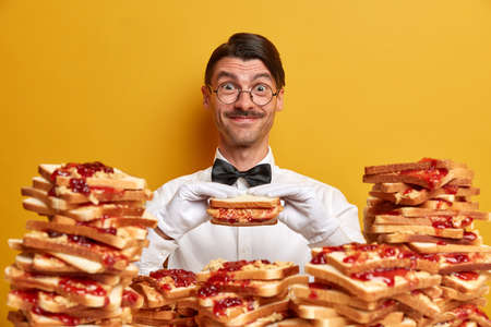 Happy friendly waiter has opportunity to taste delicious sandwich, poses near pile of bread toasts, wears formal outfit and white gloves, isolated on yellow background. Time for eating burgers Banque d'images