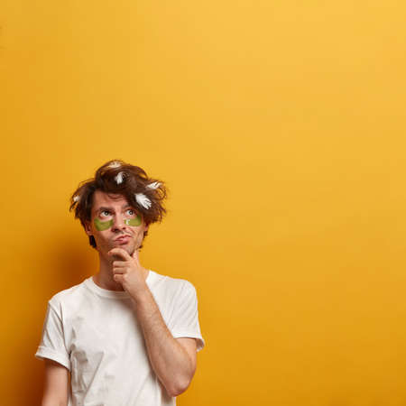 Pensive man holds chin, tries to solve problem, concentrated above, daydreams in morning, has messy hair, feathers from pillow, wears white t shirt, stands against yellow background, empty space